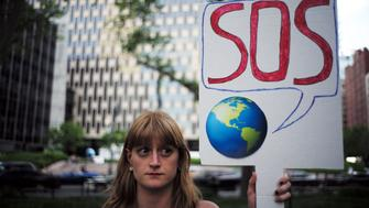 A woman displays a placard during a demonstration in New York on June 1, 2017, to protest US President Donald Trump's decision to pull out of the 195-nation Paris climate accord deal.  US President Donald Trump earlier announced America is 'getting out' of a deal he said imposed 'draconian' burdens that would cost the US millions of jobs and billions in cold hard cash.  / AFP PHOTO / Jewel SAMAD        (Photo credit should read JEWEL SAMAD/AFP/Getty Images)