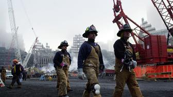 One month after the terrorist attacks on the World Trade Center, firefighters walk past the wreckage to a memorial service  October 11, 2001, in New York. A short ceremony marking the attack was held at ground zero of the center ruins.  Construction workers, police officers and firefighters took off their helmets as work on the giant demolition site ground to a halt in memory of the more than 5,200 people dead or missing following the collapse of the twin towers one month ago today. (AP Photo/pool, Stan Honda)