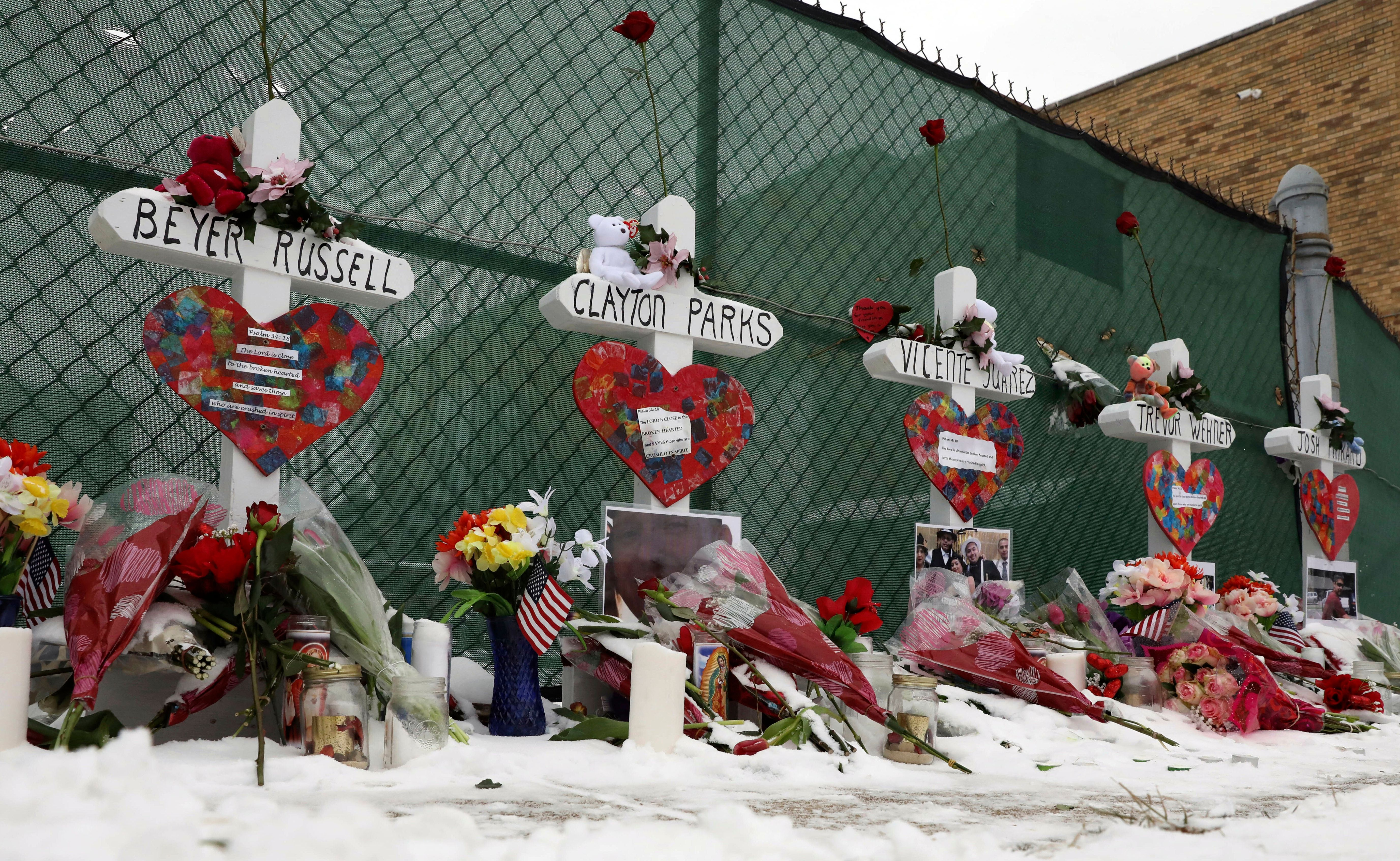 Crosses are placed for the victims of a mass shooting Sunday, Feb. 17, 2019, in Aurora, Ill., near Henry Pratt Co. manufacturing company where several were killed on Friday. Authorities say an initial background check five years ago failed to flag an out-of-state felony conviction that would have prevented a man from buying the gun he used in the mass shooting. (AP Photo/Nam Y. Huh)