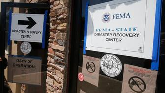 FEMA Disaster Recovery signs direct residents to help at City Hall in Rainelle, W. Va., Tuesday, Aug. 23, 2016. The town is rebuilding after floods killed five people in late June. So far, almost 8,800 people statewide have applied for FEMA individual aid, and $39.2 million has been awarded. (AP Photo/Steve Helber)