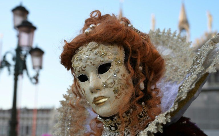 A masked reveller poses in Venice, Italy's Riva degli Schiavoni on the opening day of the Venice Carnival (AFP Photo/Vincenzo PINTO)