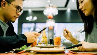 Man text messaging on smartphone while having meal with girlfriend in a restaurant