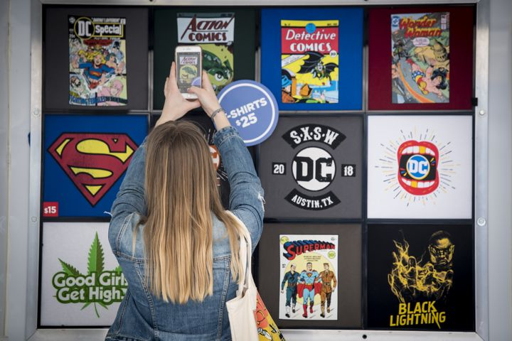 An attendee takes a photograph of DC comic book-themed shirts for sale at the South By Southwest conference in Austin, Texas,