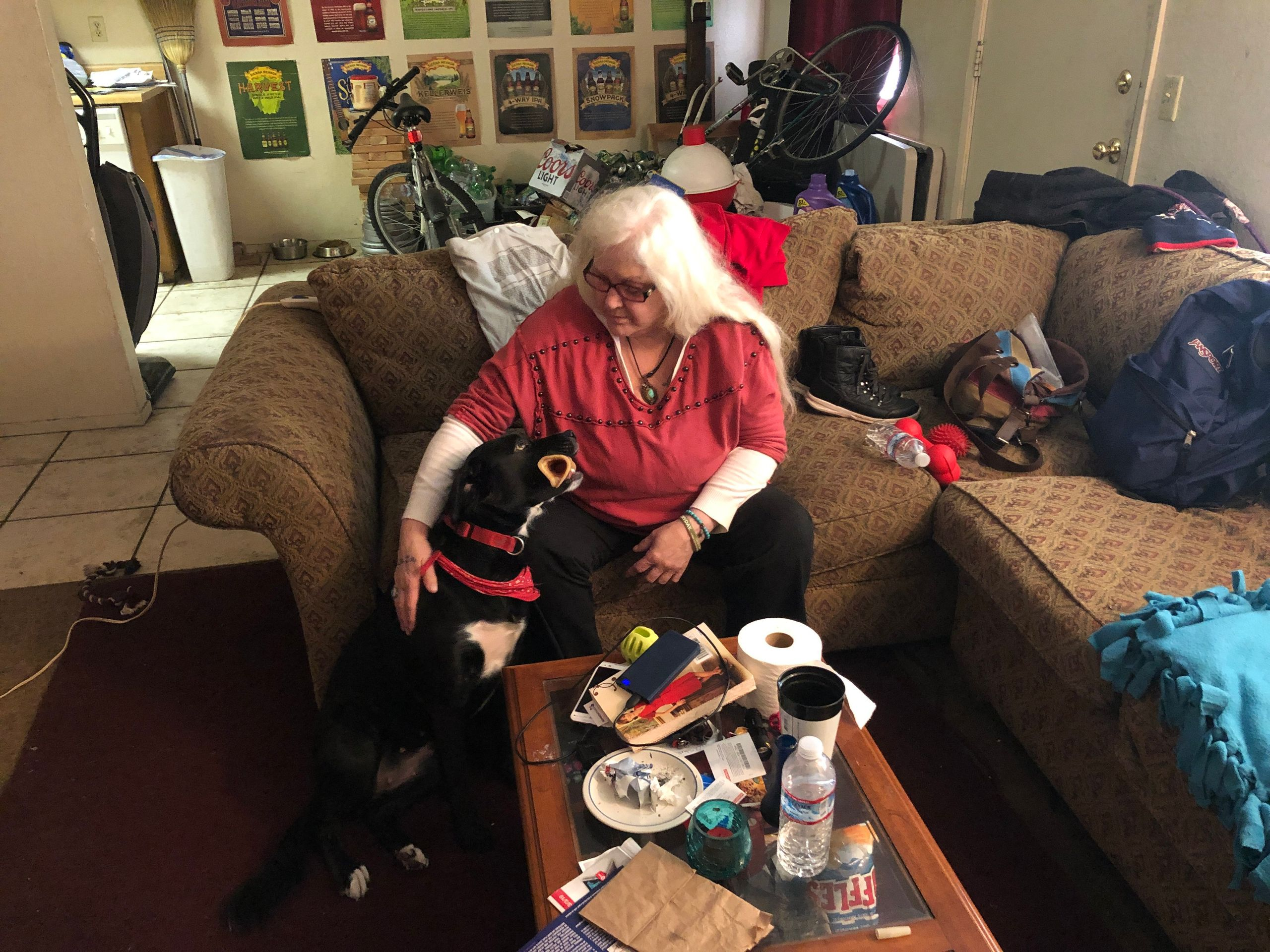 Jill David, with her dog, Ivy, has been sleeping on her son's sofa since losing her home to the Camp fire. — Chico, Cal
