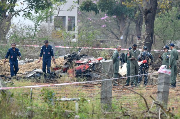 Indian Air Force personnel gather around the wreckage of one Surya Kiran 'Hawk' aircraft after two of...