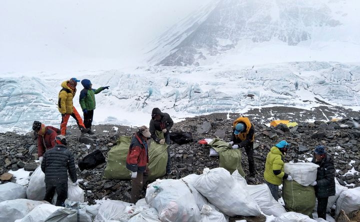 In this May 8, 2017, file photo released by Xinhua News Agency, people collect garbage at the north slope of Mount Everest in