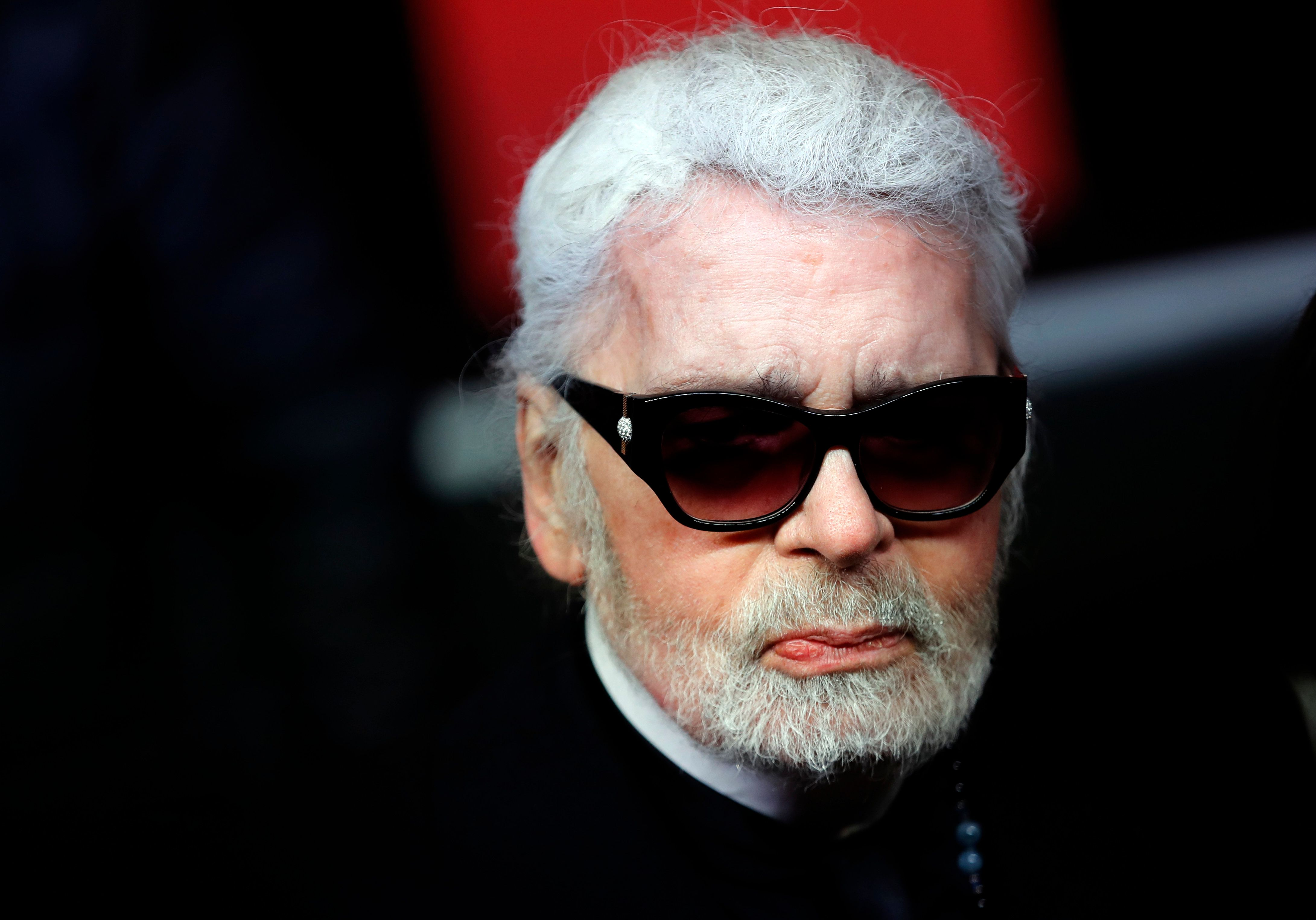 FILE  - In this Thursday, Nov. 22, 2018 file photo, Fashion designer Karl Lagerfeld poses during the Champs Elysee Avenue illumination ceremony for the Christmas season, in Paris. Chanel's octogenarian designer Karl Lagerfeld, who has looked increasingly frail in recent seasons, did not come out to take a bow at the house's couture show in Paris, something the company attributed to him being tired, it was reported on Tuesday, Jan. 22, 2019.  It is the first time in recent memory that Lagerfeld, who has designed for the house since 1983, has not come out to receive applause at the end of one of his shows. (AP Photo/Christophe Ena, File)