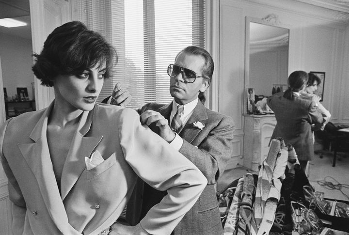 Karl Lagerfeld fits one of his designs on top model Ines de la Fressange at Chloe's Paris studio in 1983.