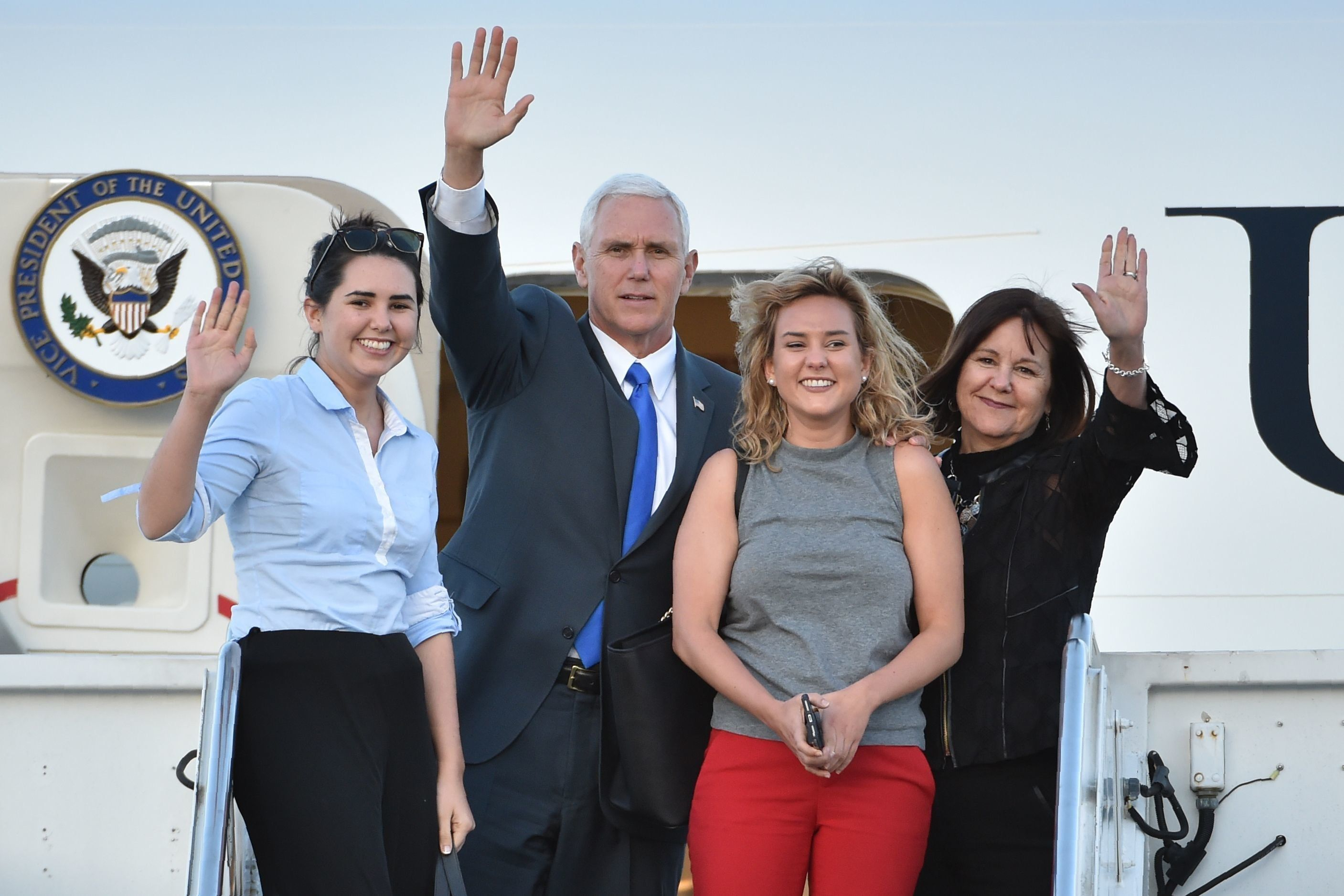 US Vice President Mike Pence (2nd L), his wife Karen (R), and their two daughters Audrey (L) and Charlotte (2nd R) wave as they depart Japan from the US naval air facility in Atsugi, Kanagawa prefecture on April 19, 2017. Pence is in the region to reassure allies fretting over Pyongyang's quickening missile programme, and its apparent readiness to carry out another banned nuclear test in its quest to develop an atomic weapon that can hit the US mainland.  / AFP PHOTO / Kazuhiro NOGI        (Photo credit should read KAZUHIRO NOGI/AFP/Getty Images)