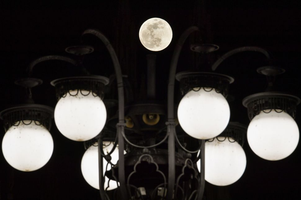 The super snow moon is pictured against street lights of Piazza del Duomo in downtown Milan.