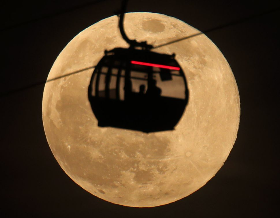 Emirates Airline cable cars are silhouetted against the backdrop of the super snow moon in Greenwich, London.