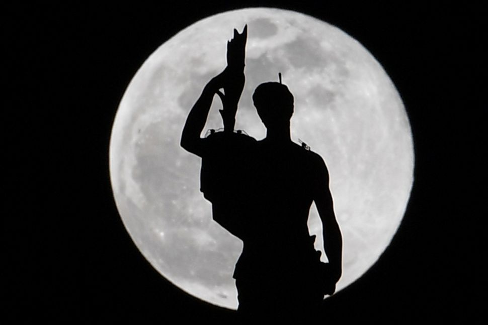 A statue atop Milan's Duomo Cathedral is pictured as the super snow moon rises.