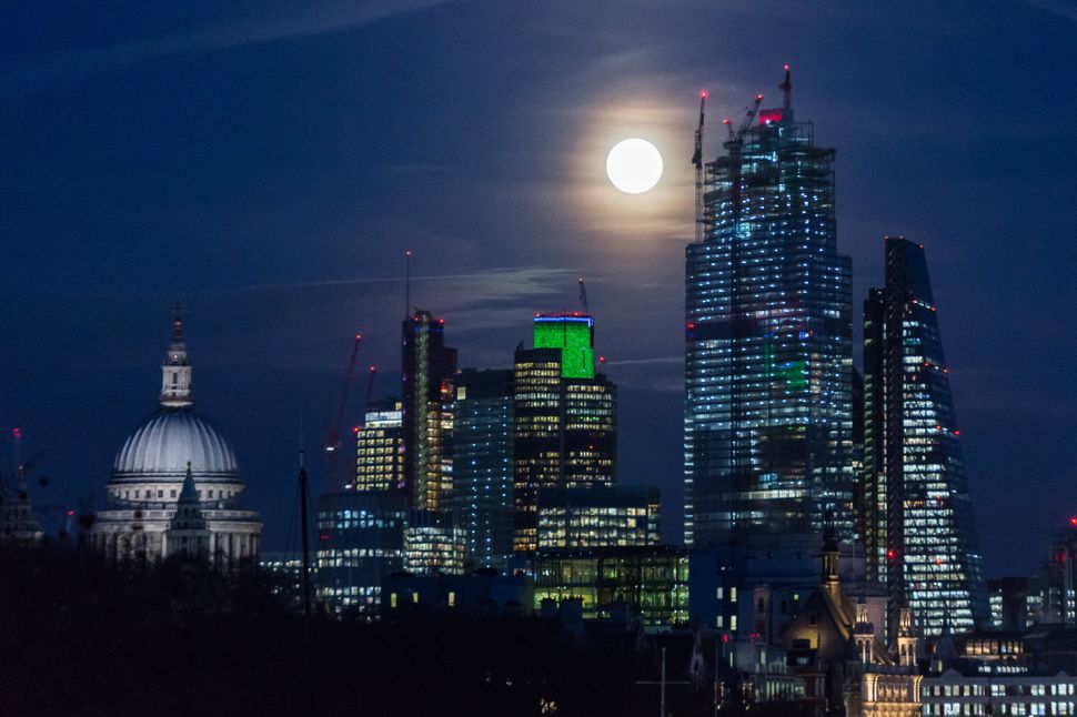 The super snow moon, also called full hunger moon, rises above central London.