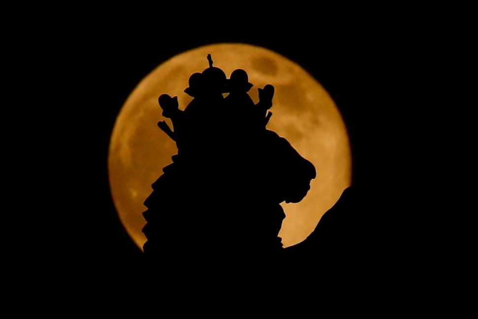The supermoon is seen behind the silhouette of Russia's coat of arms at the State Historical Museum Manezhnaya Square in Mosc