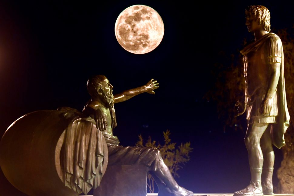 The super snow moon rises between the statues of Alexander the Great (right) and Diogenes of Sinope (left) in Corinth, Greece