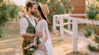 boho-style newlyweds walk in nature, summer day