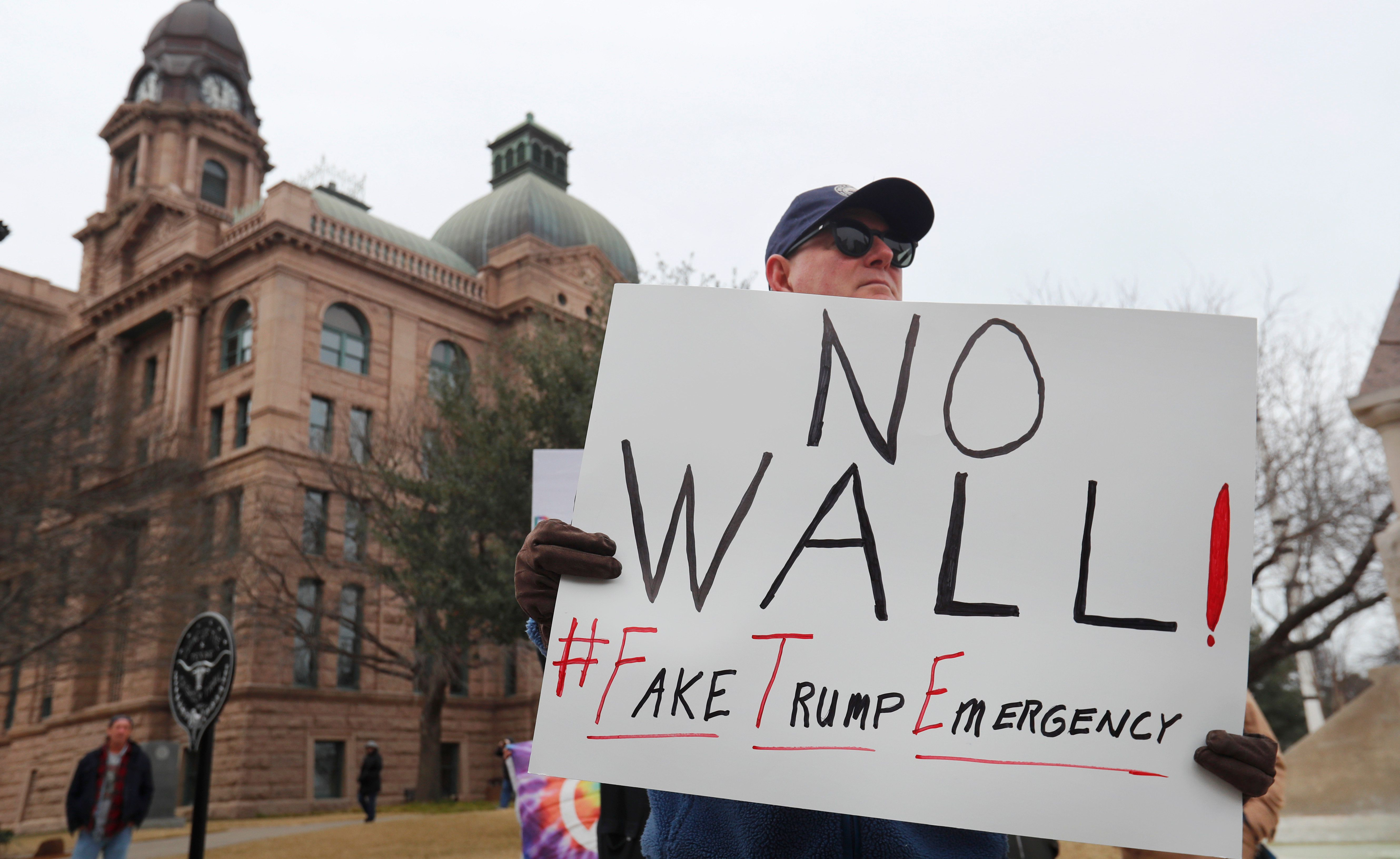 Jay Platt holds a sign during a protest in downtown Fort Worth, Texas, Monday, Feb. 18, 2019. People gathered on the Presidents Day holiday to protest President Donald Trump's recent national emergency declaration. (AP Photo/LM Otero)