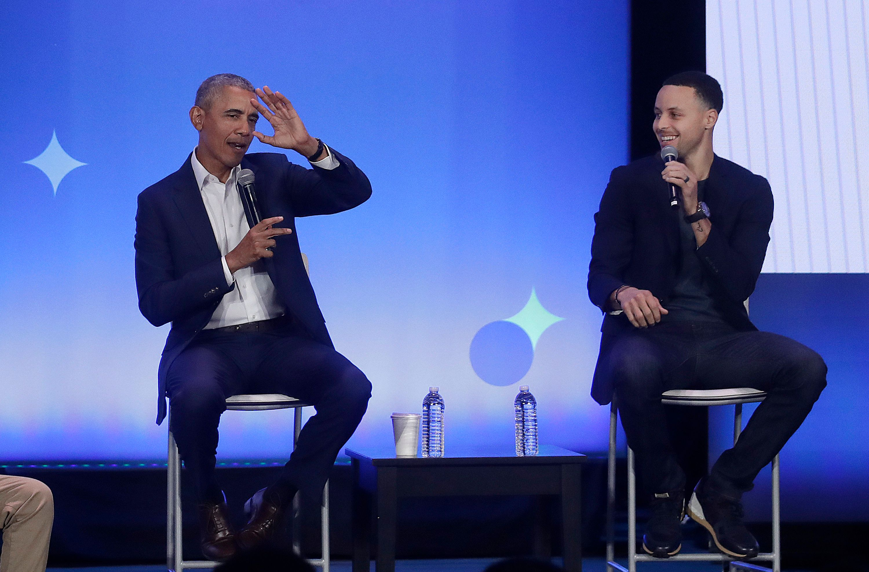 Former President Barack Obama, left, gestures as Golden State Warriors basketball player Stephen Curry laughs while speaking at the My Brother's Keeper Alliance Summit in Oakland, Calif., Tuesday, Feb. 19, 2019. (AP Photo/Jeff Chiu)