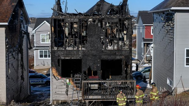 Firefighters investigate following a house fire in the Spryfield community in Halifax, Nova Scotia, Tuesday, Feb. 19, 2019. Seven children, all members of a Syrian family who arrived in Canada about two years ago, died in the early morning fire Tuesday that witnesses said quickly engulfed a home in a Halifax suburb. (Darren Calabrese/The Canadian Press via AP)