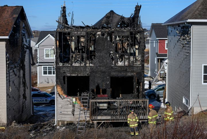 Firefighters investigate a house fire in the Spryfield community in Halifax, Nova Scotia, that claimed the lives of seven chi