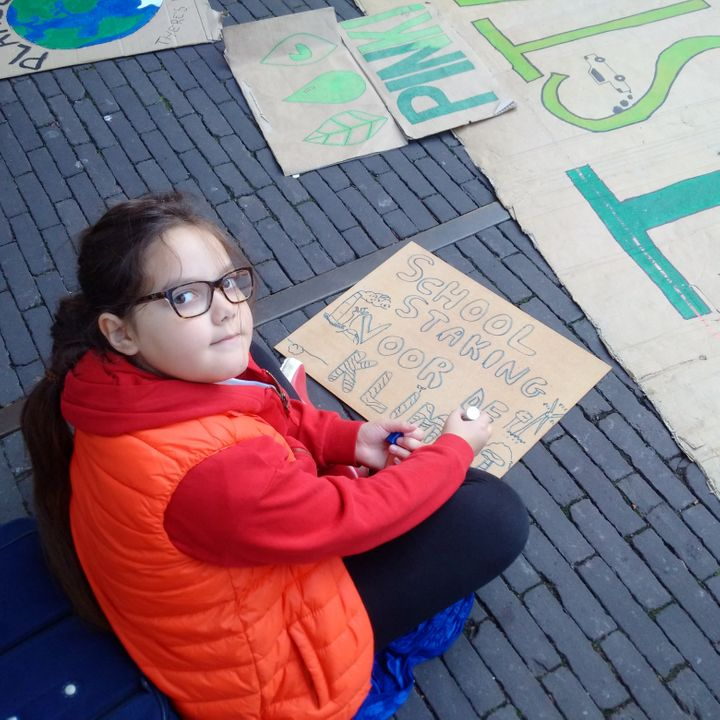 "Lilly Platt making a placard reading ""school strike for climate"" at the Hague in the Netherlands. She ditches school every Fr"