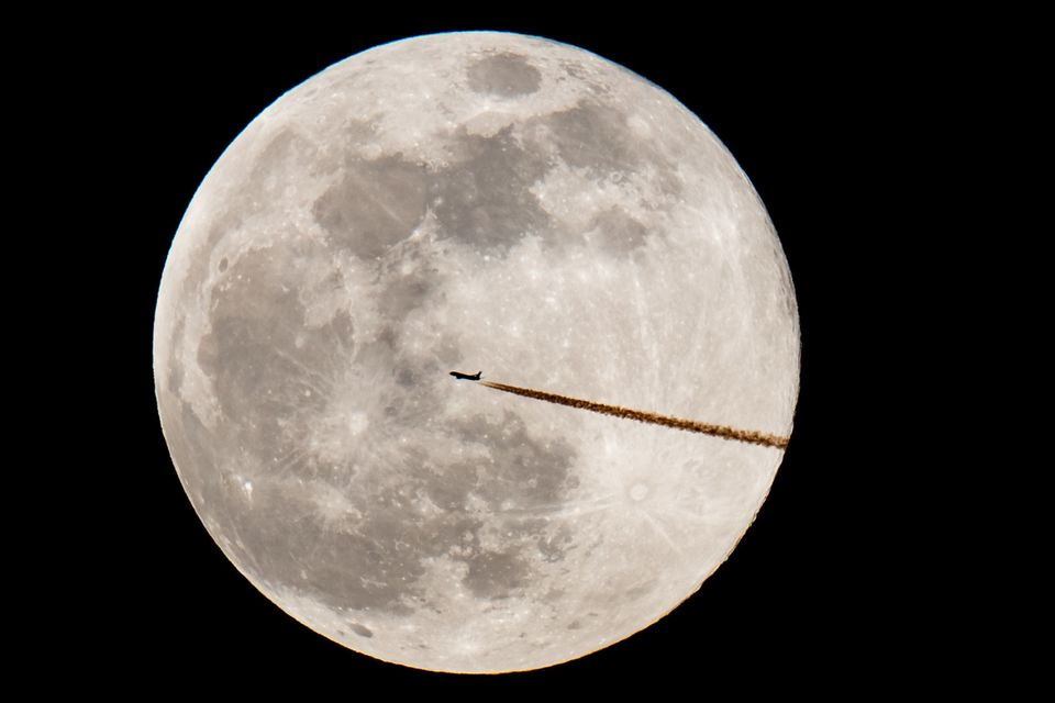An airplane is seen against the supermoon on Feb. 19, in a photo taken from Nuremberg, southern