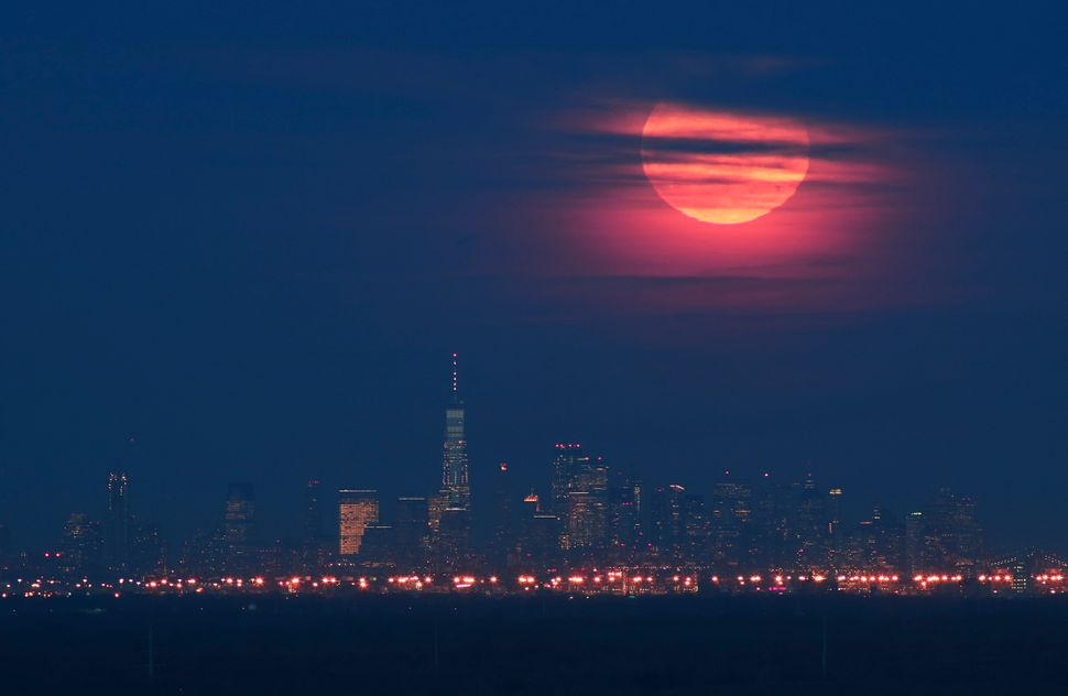 The super snow moon rises behind lower Manhattan and One World Trade Center in New York City.