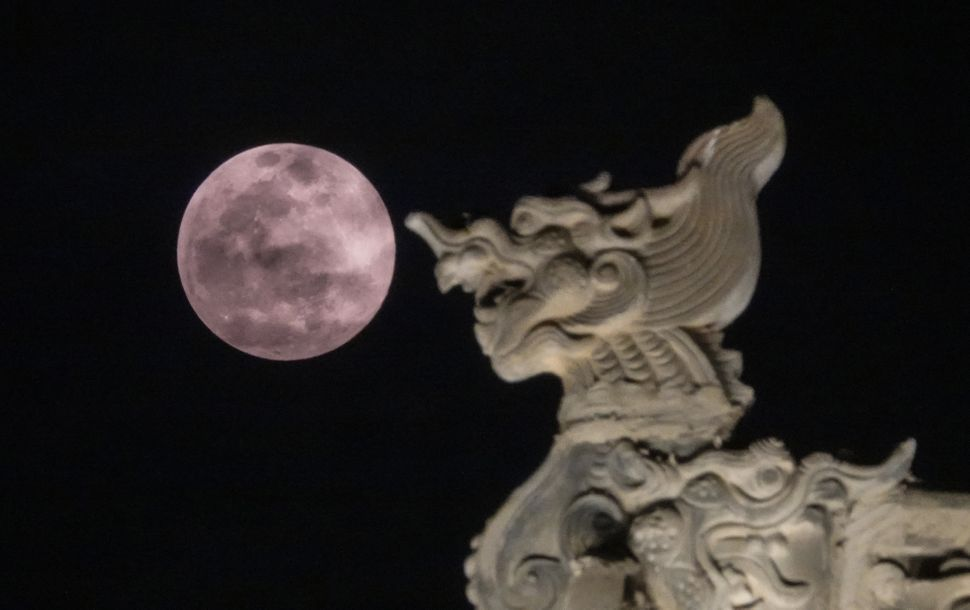 The supermoon is seen against the house ridge during the Lantern Festival in Zhengzhou, Henan Province of China.