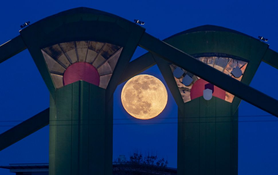 The supermoon can be seen behind pillars of the Floesserbruecke bridge in Frankfurt am Main, western Germany.