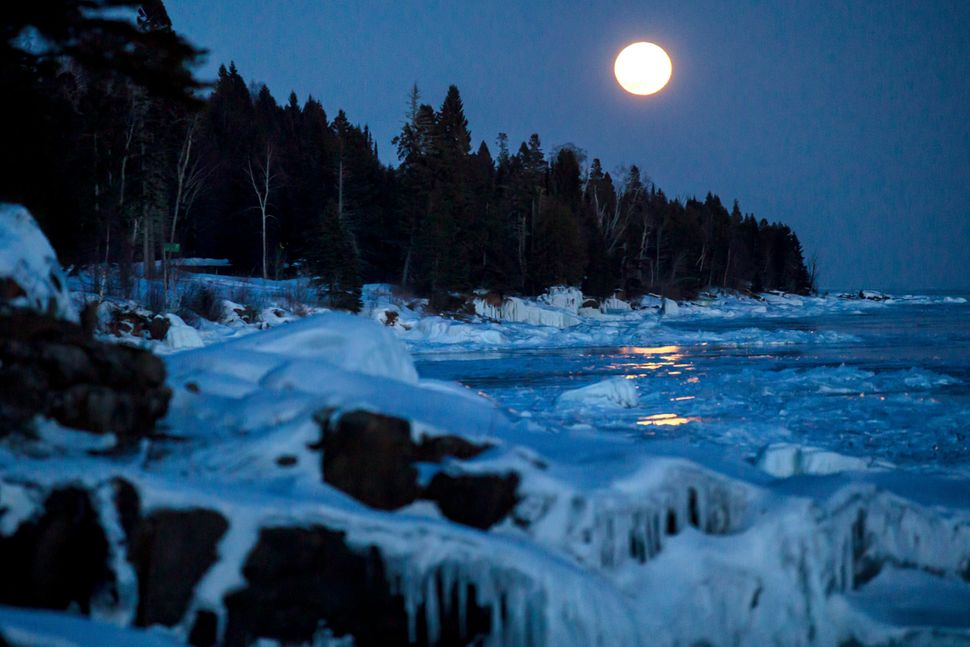 A supermoon rises over the ice on the shore of Lake Superior in Lutsen, Minnesota.