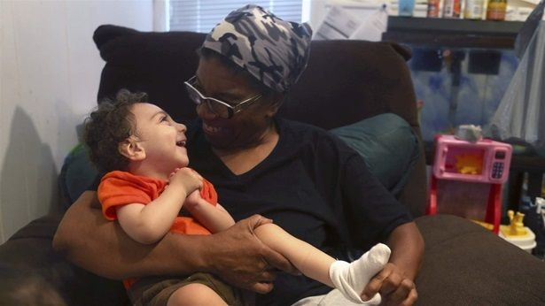 A disabled foster child smiles as he sits on his foster parent's lap at their home in Philadelphia. More children with specia