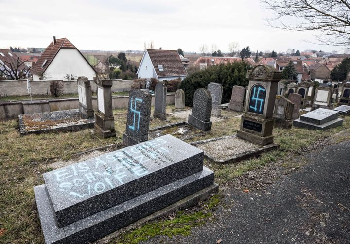 Vandalized tombs tagged with swastikas are pictured in the Jewish cemetery of Quatzenheim, in eastern France, on Feb.19, 2019