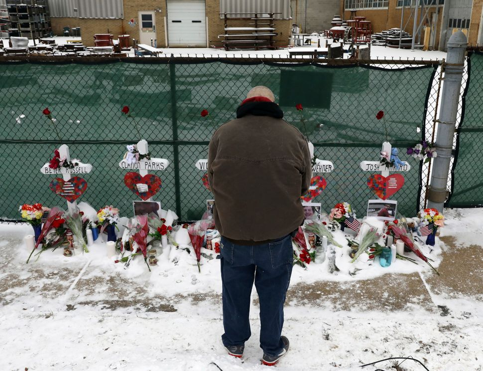 A man pays his respects at a makeshift memorial in Aurora, Illinois, near the Henry Pratt manufacturing company, where a gunm