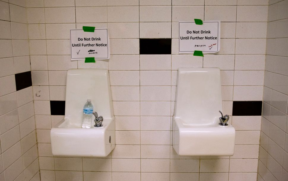 Water fountains with signs warning against drinking from them at a high school in Flint, Michigan, in May 2016. In 2014 the c