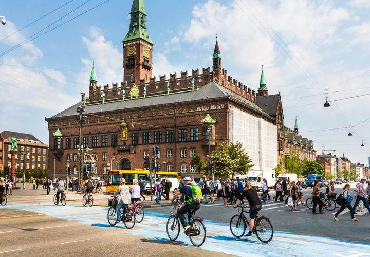 Cyclists cross the street on a dedicated bike line in front of the city hall in Copenhagen, Denmark.