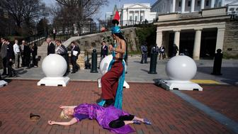 Two Equal Rights Amendment supporters, Michelle Sutherland, standing, and Natalie White, demonstrate to recreate what looks to be a similar image on the flag of Virginia, outside the state Capitol in Richmond, Va., Monday, Feb. 18, 2019. Police said 45-year-old Sutherland was later charged with indecent exposure in a protest related to the ERA. (Bob Brown/Richmond Times-Dispatch via AP)
