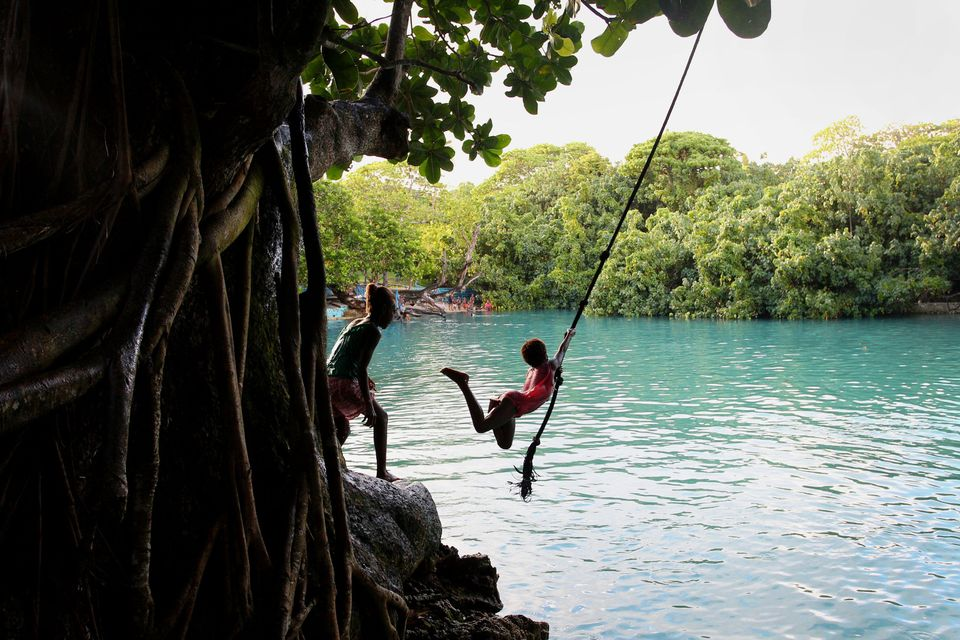 Young local children play at the Blue Lagoon swimming hole in Efate, Vanuatu. The island nation banned single-use plastic bags, straws and polystyrene food containers last year, in an effort to safeguard ocean health and cut back on urban pollution.