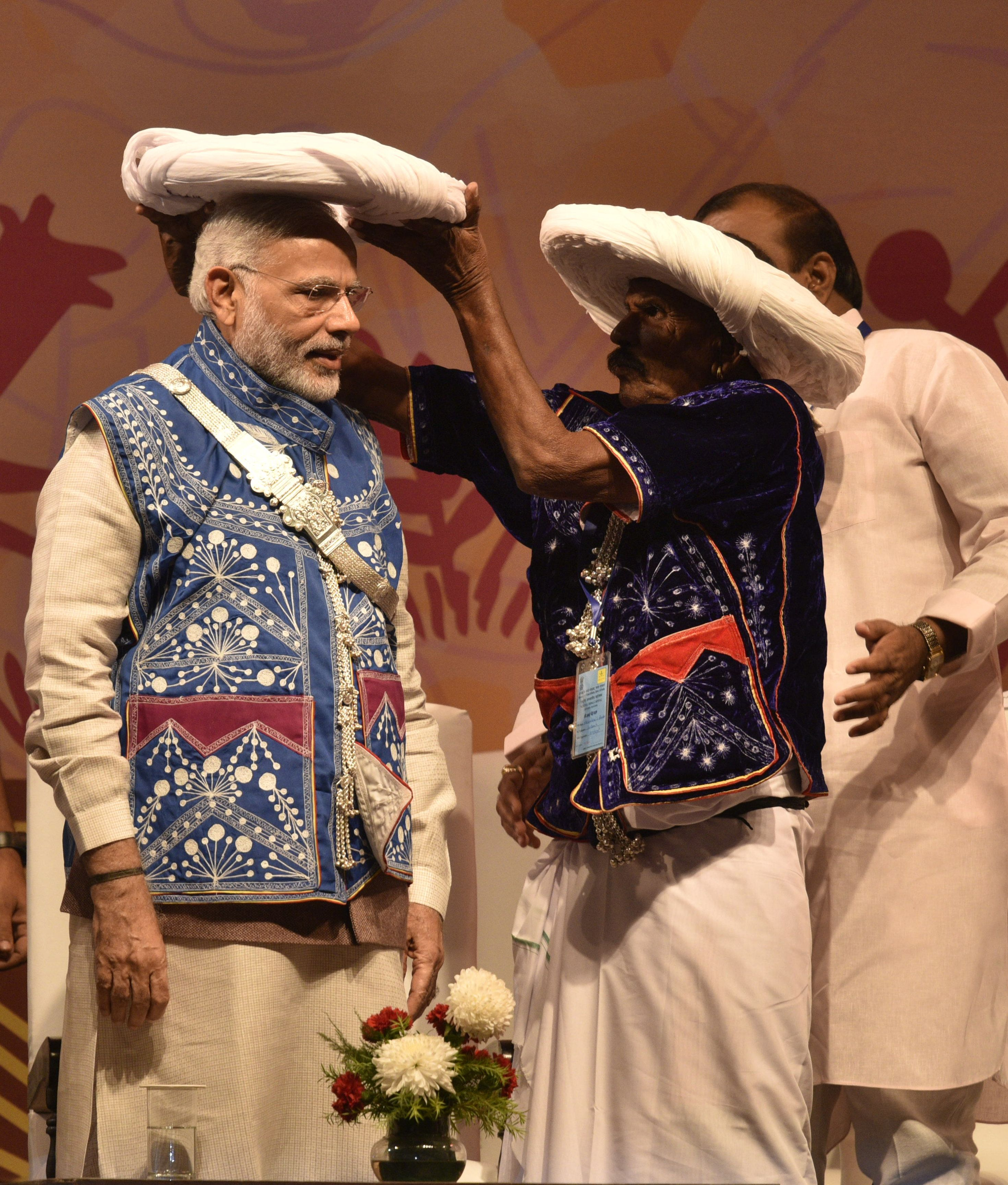 Prime Minister Narendra Modi, in tribal attire, being offered a traditional turban at the inauguration...