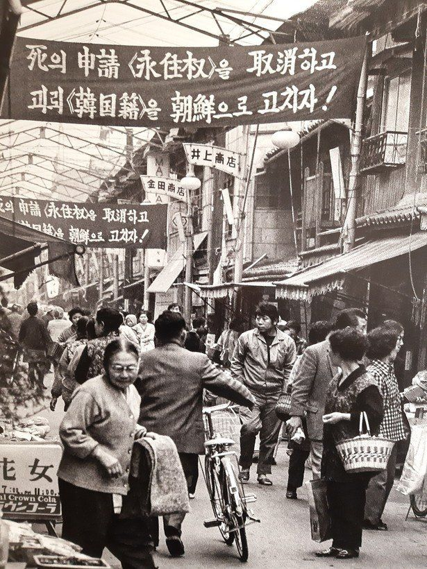 조지현 작가가 찍은 60년대말 오사카 이카이노의 조선 시장 풍경. 영주권을 죽음의 신청이라고 비난하며 한국적을 조선으로 고치자는 총련의 플랭카드가