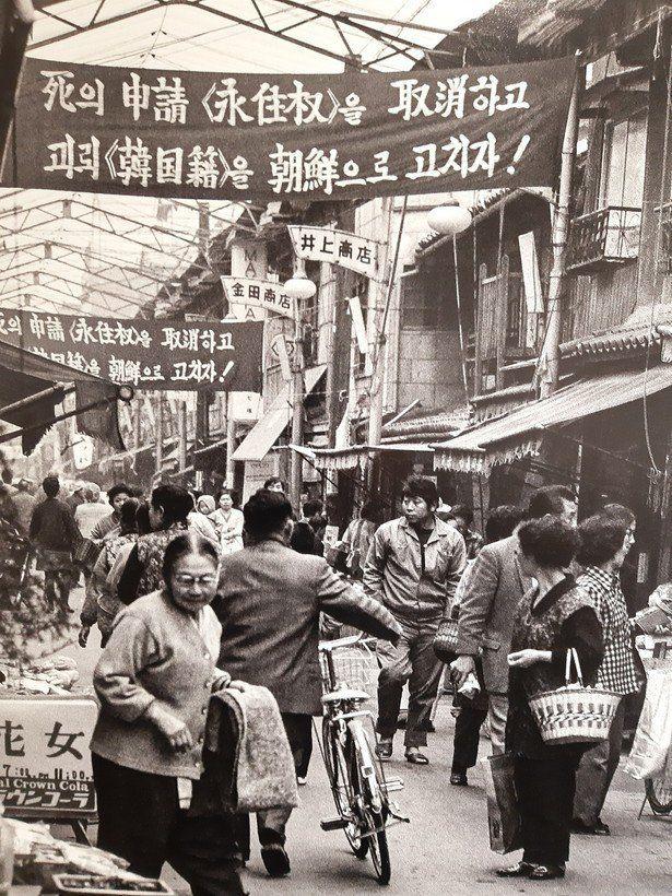 조지현 작가가 찍은 60년대말 오사카 이카이노의 조선 시장 풍경. 영주권을 죽음의 신청이라고 비난하며 한국적을 조선으로 고치자는 총련의 플랭카드가 붙어있다.