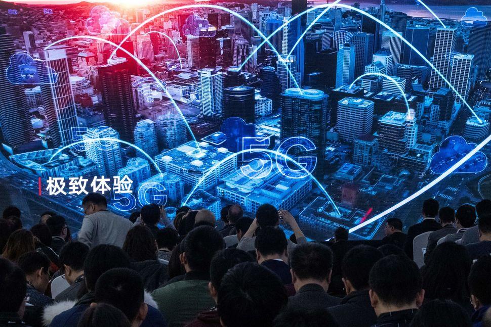 중국 베이징에 위치한 화웨이 브리핑 센터에서 열린 5G 제품 발표 기자회견에 참석한 언론인과 초대객들이 홍보 영상을 지켜보고 있다. 2019년
