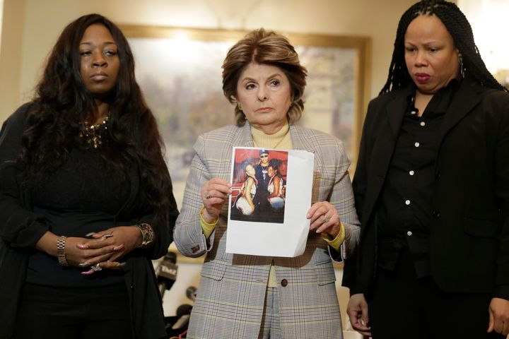 Latresa Scaff (R) and Rochelle Washington (L) look on as attorney Gloria Allred holds up a picture of them as teenagers on th