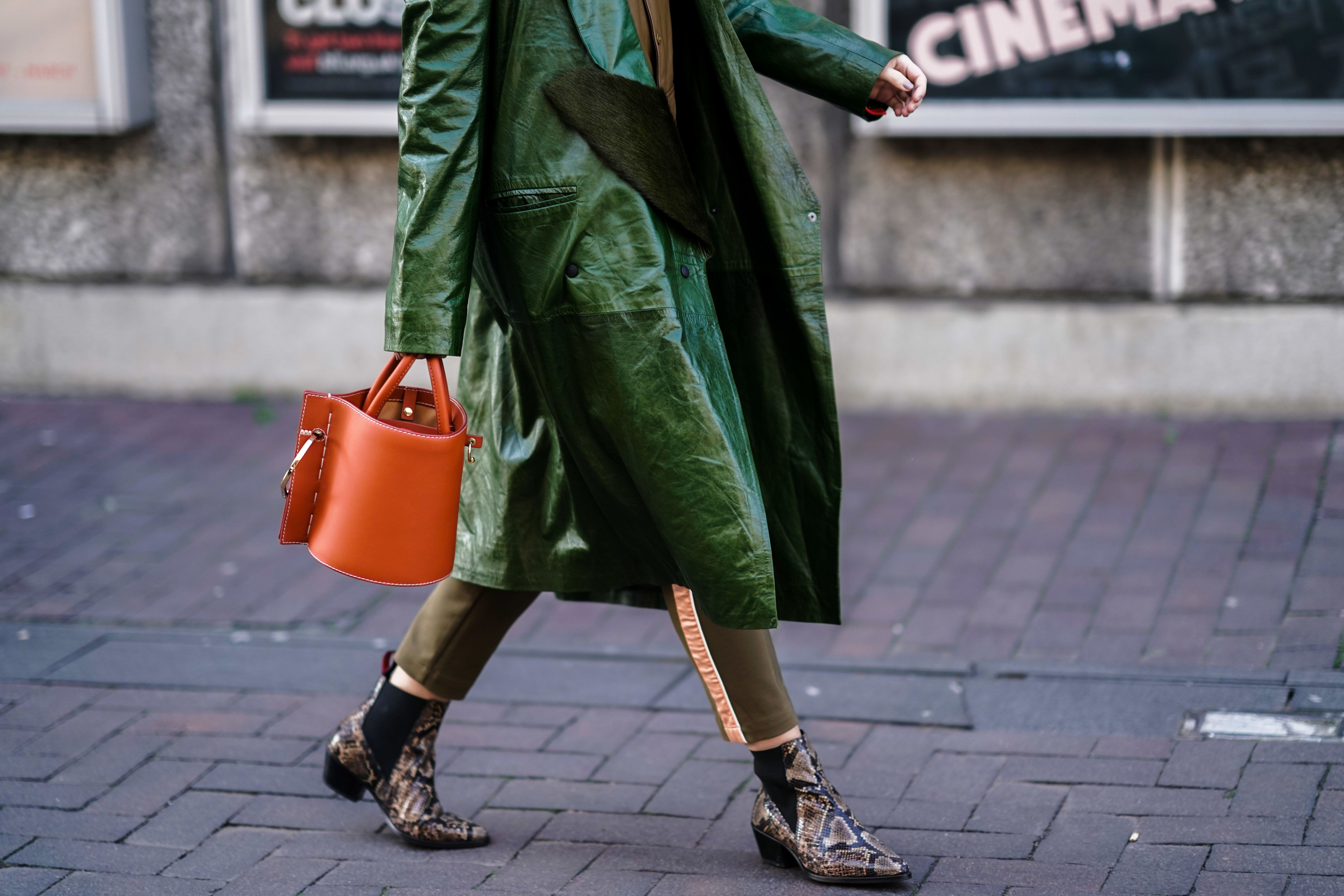 LONDON, ENGLAND - FEBRUARY 17: Andreea Cristea wears a green leather trench coat, a brown shirt, an orange bag, snake print shoes, during London Fashion Week February 2019 on February 17, 2019 in London, England. (Photo by Edward Berthelot/Getty Images)