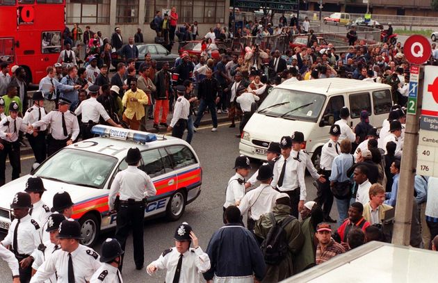 A police car leads a van transporting the five murder suspects away from the crowds of angry demonstrators after the two days of questioning in the Stephen Lawrence Murder Inquiry came to an end