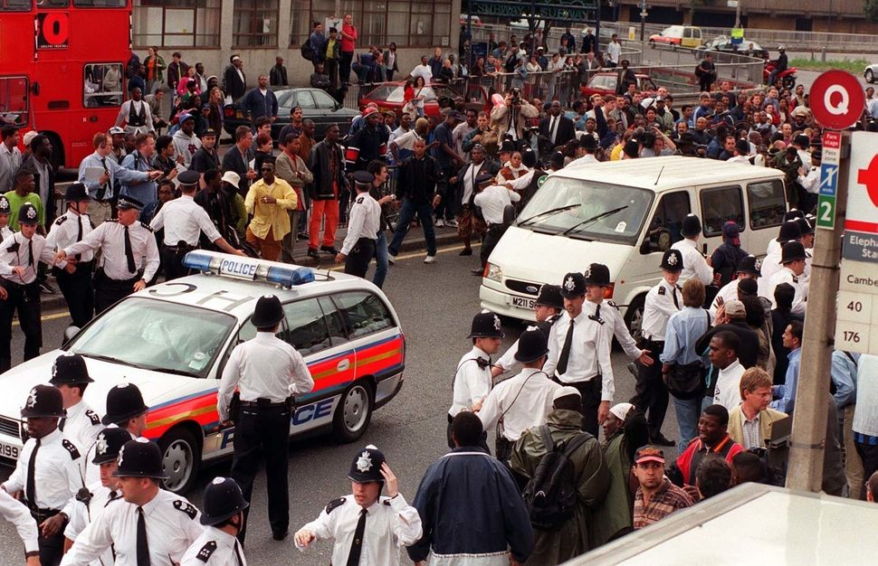A police car leads a van transporting the five murder suspects away from the crowds of angry demonstrators...