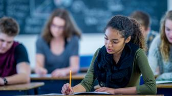A multi-ethnic group of high school students are indoors in their classroom. A girl of African descent is in focus, and she is writing a test with her pencil.