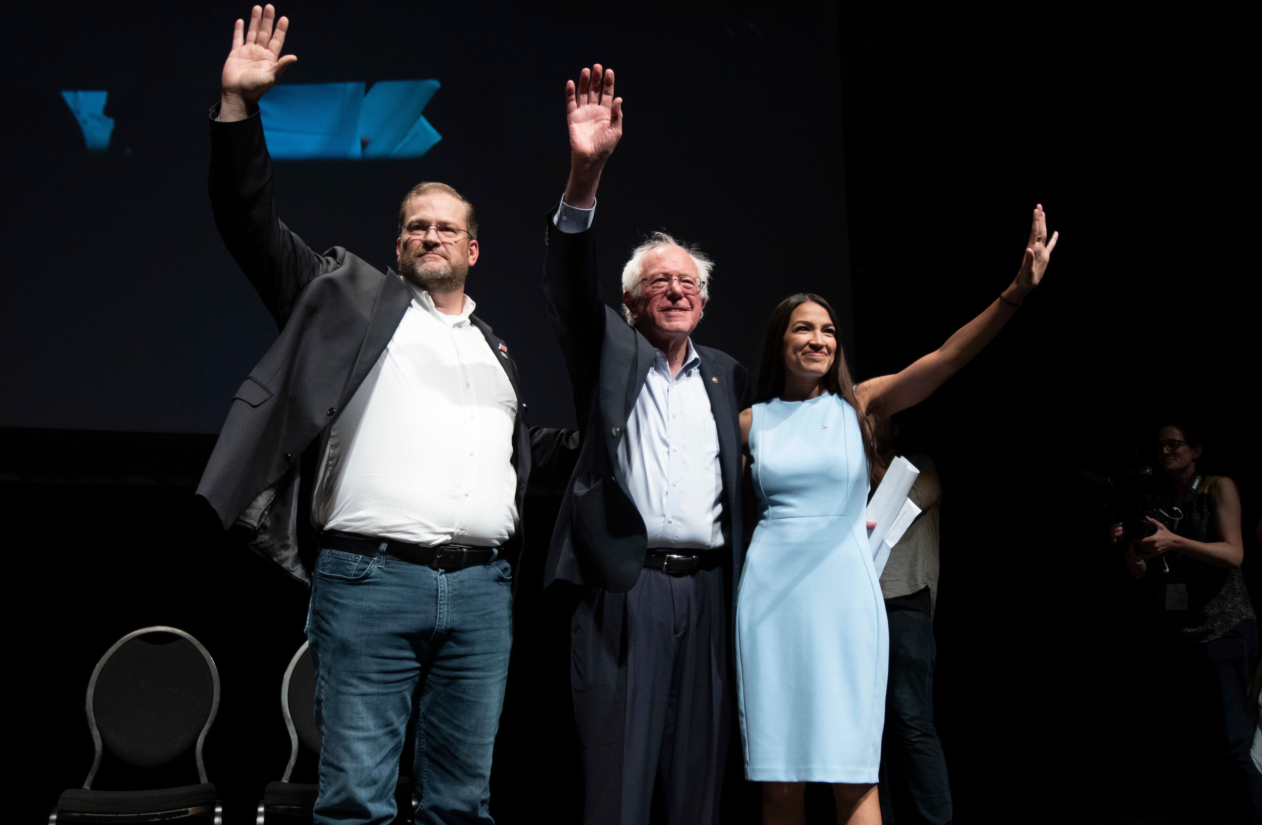 WICHITA, KA - JULY 20: James Thompson, Senator Bernie Sanders and Alexandria Ocasio-Cortez,  wave to the crowd at the end of a campaign rally in Wichita, Kansas on July 20, 2018.  (Photo by J Pat Carter for the Washington Post)