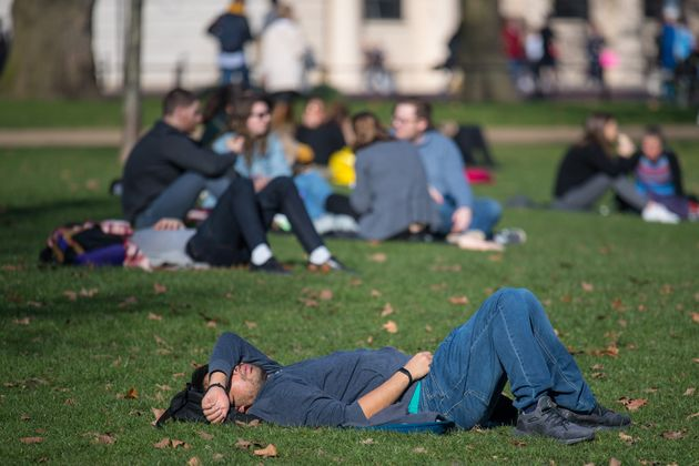 People sit in the sun in London's St James's Park on Saturday.