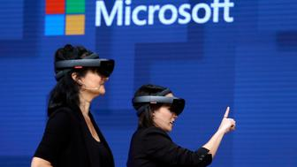 FILE- In this May 11, 2017, file photo, members of a design team at Cirque du Soleil demonstrate use of Microsoft's HoloLens device in helping to virtually design a set at the Microsoft Build 2017 developers conference in Seattle. Federal contract records show the U.S. Army has awarded Microsoft a $480 million contract to supply its HoloLens headsets to soldiers. The head-mounted displays use augmented reality, which means viewers can see virtual imagery superimposed over the real-world scenery in front of them. Microsoft says the technology will provide troops with better information to make decisions.(AP Photo/Elaine Thompson, File)