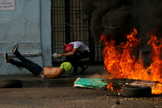 A demonstrator, left, falls after getting caught in a strand of barbed wire during clashes with the Bolivarian...